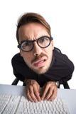 Durchdachter Geschäftsmann mit Gläsern unter Verwendung des Computers Lizenzfreie Stockfotos