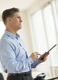 Durchdachter Geschäftsmann Looking Away While, das Digital-Tablet hält Lizenzfreie Stockfotos