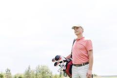Durchdachter Golfspieler von mittlerem Alter, der während Tragetasche gegen klaren Himmel weg schaut Stockfoto