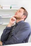 Durchdachter gutaussehender Mann bei der Arbeit Lizenzfreies Stockbild