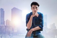 Durchdachter Jugendlicher, der seine Hand unter dem Kinn hält Stockfotografie