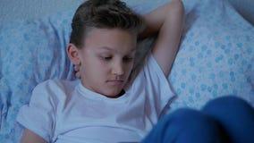 Durchdachter Jugendlichjunge, der im Bett, Berührentablettenschirm liegt stock footage