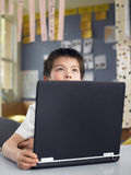 Durchdachter Junge, der durch Laptop im Klassenzimmer sitzt stockfotografie