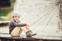 Durchdachter Junge durch den Brunnen Stockfotografie