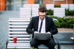 Durchdachter junger Geschäftsmann in der Klage, die auf Holzbank mit Kaffeetasse dem in der Hand und Laptop gesetzt auf seinen Sc Lizenzfreie Stockfotografie