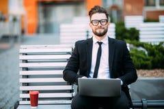 Durchdachter junger Geschäftsmann in der Klage, die auf Holzbank mit Kaffeetasse dem in der Hand und Laptop gesetzt auf seinen Sc Stockbilder