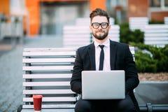 Durchdachter junger Geschäftsmann in der Klage, die auf Holzbank mit Kaffeetasse dem in der Hand und Laptop gesetzt auf seinen Sc Stockfotos