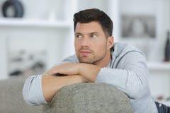 Durchdachter junger hübscher Mann auf Sofa lizenzfreies stockbild