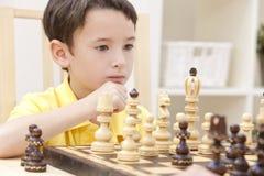 Durchdachter junger Junge, der Schach spielt Lizenzfreie Stockfotos