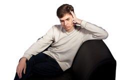 Durchdachter junger Mann auf dem Sofa stockfotos