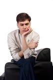 Durchdachter junger Mann auf dem Sofa lizenzfreie stockfotografie