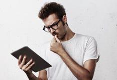 Durchdachter junger Mann mit digitaler Tablette Stockfotografie