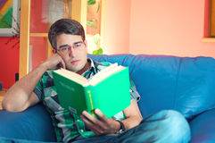 Durchdachter junger Mann mit Gläsern ein Buch lesend lizenzfreie stockbilder