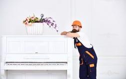 Durchdachter Kerl, der auf die Oberseite des weißen Klaviers der Weinlese mit dem Glasblumenvase lokalisiert auf weißem Hintergru Stockfotos
