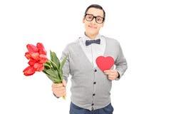Durchdachter Kerl, der ein rotes Herz und Blumen hält Lizenzfreies Stockbild