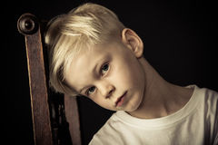 Durchdachter kleiner blonder Junge, der auf einem Stuhl sitzt Lizenzfreies Stockfoto