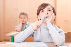 Durchdachter kleiner Junge während der Klassen Stockfotos