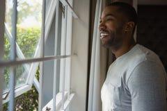 Durchdachter lächelnder Mann, der heraus zu Hause durch Fenster schaut stockbilder