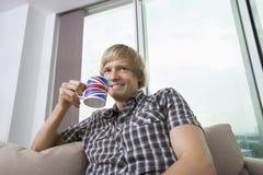 Durchdachter lächelnder Mittelerwachsenmann mit Kaffeetasse im Wohnzimmer zu Hause Stockbild