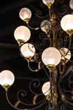 Durchdachter Leuchter hängt von einem Dach mit Art- DecoDekorationen und runden Glasbereichen lizenzfreie stockbilder