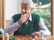 Durchdachter älterer Mann betrachtet seine vielen Pillen Lizenzfreies Stockfoto