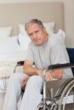 Durchdachter älterer Mann in seinem Rollstuhl Stockbild