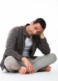 Durchdachter Mann auf dem Boden, der Kamera betrachtet Lizenzfreies Stockfoto