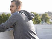Durchdachter Mann, der auf der Wand weg schaut sich lehnt Lizenzfreie Stockfotos