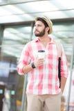 Durchdachter Mann, der beim Halten der Wegwerfschale in der Stadt weg schaut Lizenzfreies Stockfoto
