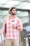 Durchdachter Mann, der beim Halten der Wegwerfschale in der Stadt weg schaut Stockbild