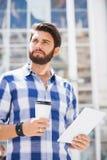 Durchdachter Mann, der beim Halten der Wegwerfschale und des Tablet-PCs in der Stadt weg schaut Lizenzfreies Stockfoto