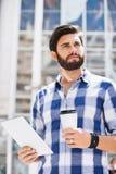 Durchdachter Mann, der beim Halten der Wegwerfschale und des Tablet-PCs in der Stadt weg schaut Lizenzfreie Stockfotografie