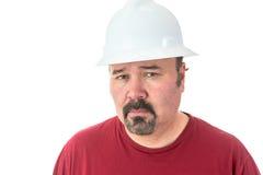 Durchdachter Mann, der einen Hardhat trägt Stockbild