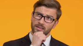 Durchdachter Mann, der sein Kinn, versuchend, Entscheidung, hellen Hintergrund zu treffen verkratzt stock video