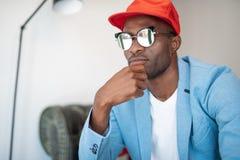 Durchdachter Mann in der Sonnenbrille, die sich nach innen entspannt stockfoto