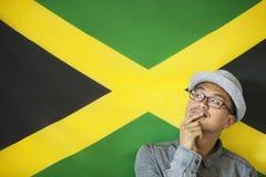 Durchdachter Mann gegen jamaikanische Flagge Lizenzfreies Stockfoto
