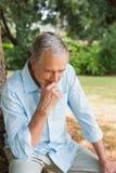 Durchdachter Mann im Ruhestand, der auf Baumstamm mit dem Kopf gebeugt sitzt Lizenzfreies Stockbild