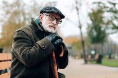 Durchdachter Mann im Ruhestand, der auf Spazierstock sich lehnt lizenzfreie stockfotografie
