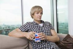 Durchdachter Mittelerwachsenmann, der zu Hause mit Kaffeetasse im Wohnzimmer sitzt Stockfoto