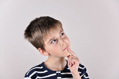 Durchdachter netter Junge, der oben schaut Stockbilder
