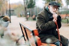 Durchdachter reifer Mann, der auf Spazierstock sich lehnt lizenzfreie stockfotografie