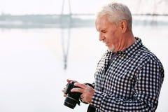 Durchdachter reifer Mann, der mit Kamera dokumentiert lizenzfreies stockfoto