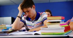 Durchdachter Schüler, der im Klassenzimmer sitzt stock video footage