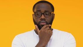 Durchdachter schwarzer Student, der das Kinn, nach Entscheidung suchend zuckt und berührt stock video footage