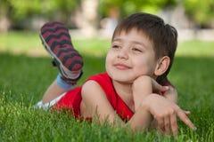 Durchdachter stattlicher Junge auf dem grünen Gras Stockbild