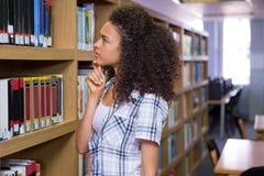 Durchdachter Student in der Bibliothek Lizenzfreies Stockbild