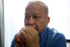 Durchdachter trauriger älterer Mann, der gehenden Stock beim Sitzen auf Stuhl hält Lizenzfreie Stockbilder