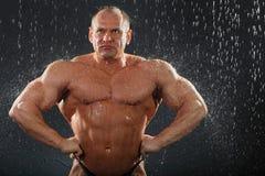 Durchdachter unbearbeiteter Bodybuilder steht im Regen Stockfoto