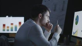 Durchdachter Wirtschaftsanalytiker, der Diagramme und Diagramme im Nachtbüro erforscht stock footage