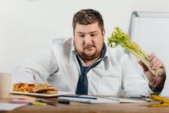 durchdachtes überladenes Geschäftsmannwählen gesund oder ungesunde Fertigkost am Arbeitsplatz lizenzfreie stockfotografie